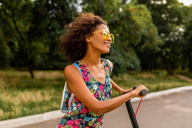 Giovane donna di colore alla moda che si diverte nel parco cavalcando scooter elettrico in stile moda estiva, vestito colorato hipster, indossando zaino e occhiali da sole gialli