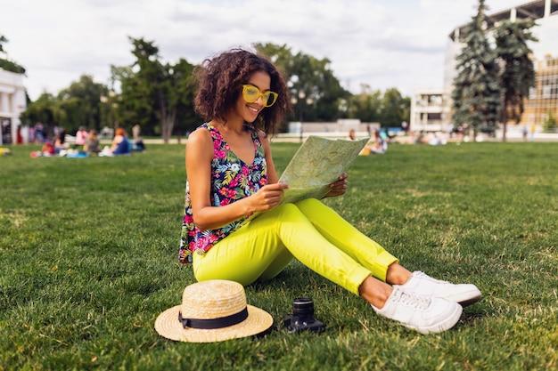 Giovane donna di colore alla moda che si diverte nello stile di moda estiva del parco, vestito colorato hipster, seduto sull'erba, viaggiatore con una mappa e cappello di paglia