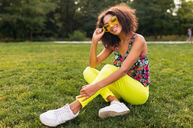 Young stylish black woman having fun in park summer fashion style, colorful hipster outfit, sitting on grass wearing yellow sunglasses and trousers, sneakers