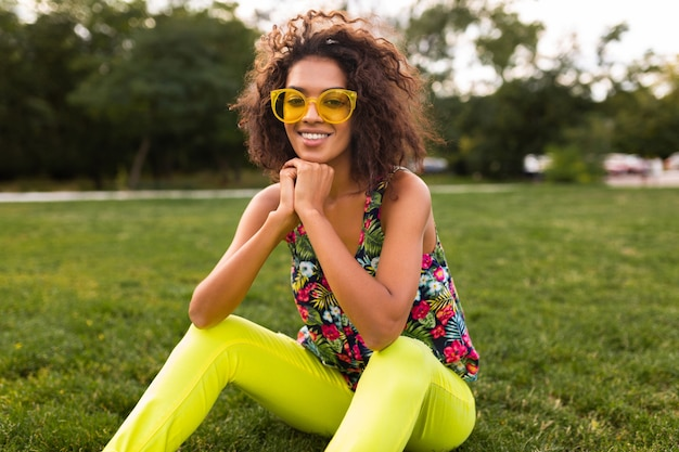 Young stylish black woman having fun in park summer fashion style, colorful hipster outfit, sitting on grass