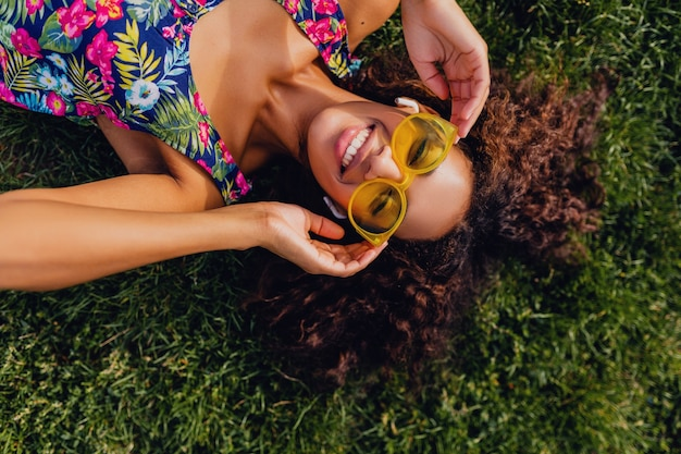 Young stylish black woman listening to music on wireless earphones having fun lying on grass in park, summer fashion style, colorful hipster outfit, view from above