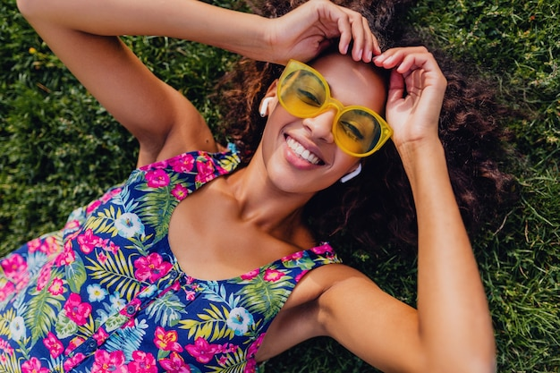 Giovane donna di colore alla moda che ascolta la musica sugli auricolari wireless divertendosi sdraiato sull'erba nel parco, stile di moda estiva, vestito colorato hipster, vista dall'alto