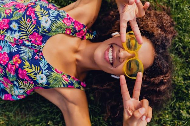 Giovane donna di colore alla moda che ascolta la musica sugli auricolari wireless divertendosi nel parco, stile di moda estiva, vestito colorato hipster, sdraiato sull'erba, vista dall'alto