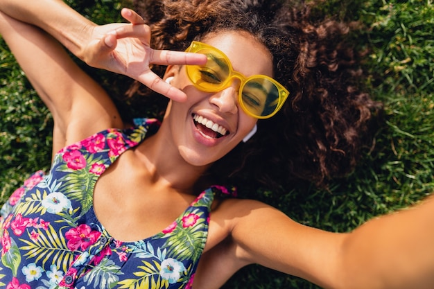 Young stylish black woman listening to music on wireless earphones having fun in park, summer fashion style, colorful hipster outfit, lying on grass, view from above