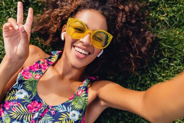Молодая стильная темнокожая женщина, слушающая музыку на беспроводных наушниках, веселится в парке, в летнем модном стиле, красочный хипстерский наряд, лежа на траве, вид сверху