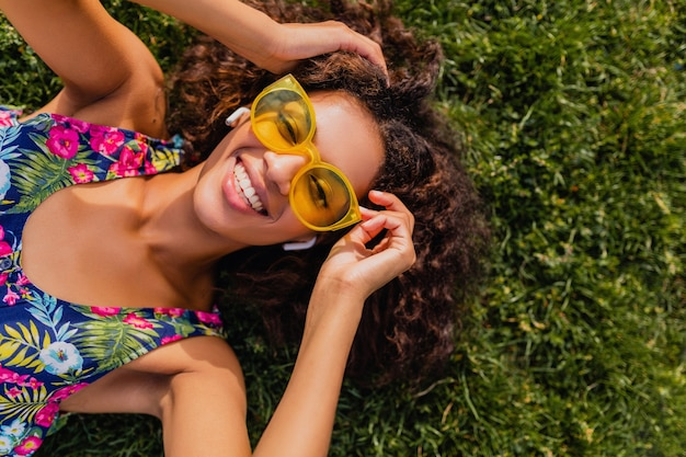 Молодая стильная темнокожая женщина, слушающая музыку на беспроводных наушниках, веселится, лежа на траве в парке, стиль летней моды, красочный хипстерский наряд, вид сверху