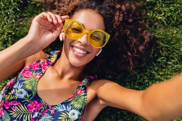 Молодая стильная темнокожая женщина, слушающая музыку на беспроводных наушниках, веселится, лежа на траве в парке, делая селфи-фото на камеру телефона, красочный хипстерский наряд в стиле летней моды, вид сверху