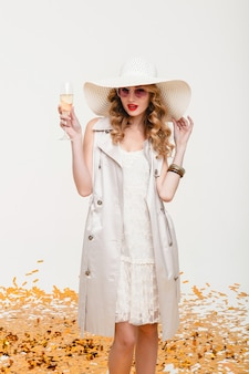 Young stylish blond woman in big hat and sunglasses holding glass of champagne
