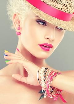 ピンクリボンの麦わら帽子に身を包んだスタイリッシュなブロンドの髪の少女は、トレンディな明るいメイクと色とりどりのマニキュアを爪に施しています。ファッション、マニキュア、化粧品。