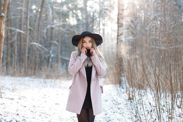 검은 유행 드레스에 분홍색 세련된 코트에 우아한 검은 모자에 젊은 세련된 금발의 여자는 겨울 숲에 서 있습니다. 아름다운 소녀는 풍경을 즐길 수 있습니다.