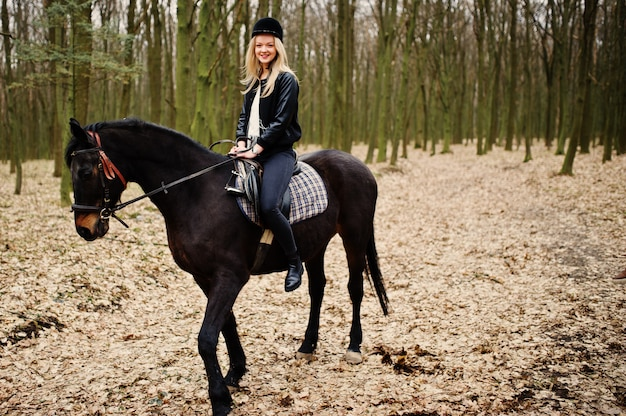 Young stylish blonde woman riding on horse at autumn forest