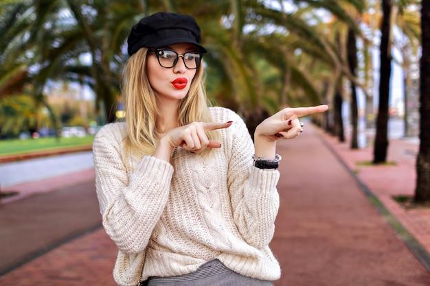 Молодая стильная блондинка показывает направление пальцами, возбужденные удивленные эмоции, модный элегантный гламурный наряд, улицы барселоны с пальмами, настроение путешествия.