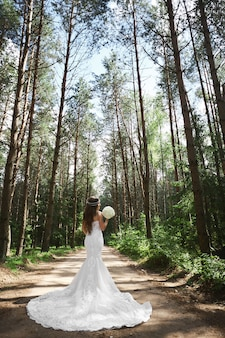 Young stylish bride with jewelry in her hairstyle in lace wedding dress keeping a bouquet and posing in the forest.