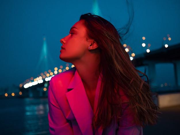 夜の街の光、ネオンの照明、彼女の顔に赤い光の中で若いスタイリッシュなブルネット。夜の街の散歩、斜張橋、背景の夜の街のパノラマの若い女性