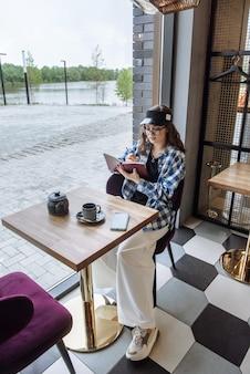 세련된 젊고 세련된 브루네트는 레스토랑에 앉아 일하는 동안 메모장에 아이디어를 씁니다.