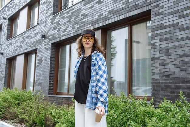 새로운 여름 옷 카탈로그 컬렉션에서 커피 컵과 함께 도시 거리의 배경에 포즈를 취하는 안경을 쓴 젊고 세련된 브루네트 여성