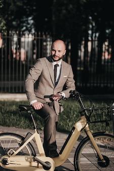 自転車で仕事に行くスーツを着た若いスタイリッシュなビジネスマン。