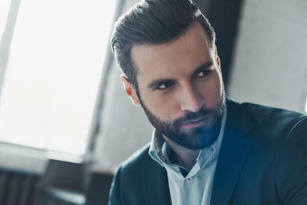 Молодой стильный бизнесмен-лидер в помещении в офисе, глядя в сторону