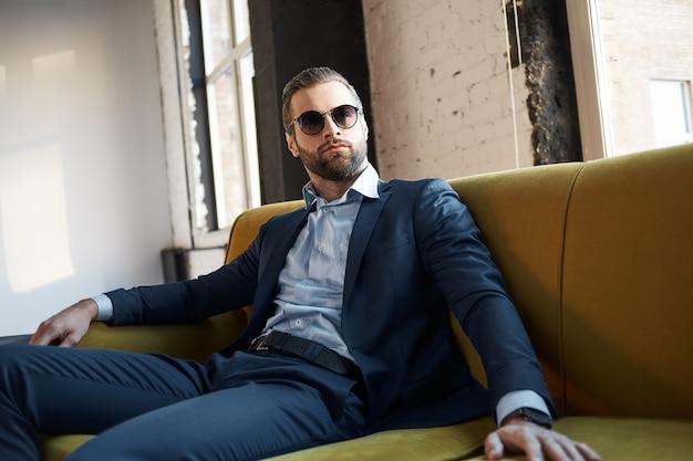 Молодой стильный бизнесмен-лидер в помещении в офисе в солнцезащитных очках, задумчиво глядя в сторону