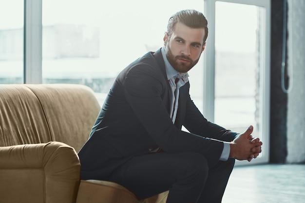 Молодой стильный бизнесмен-лидер в помещении в офисе с часами, серьезными