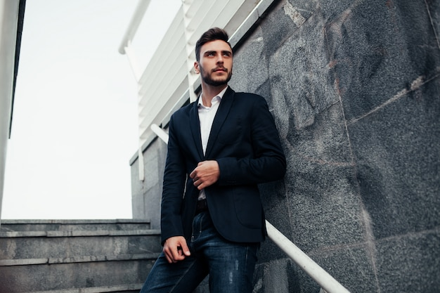 Young stylish businessman man with a beard in a fashionable suit and jeans.