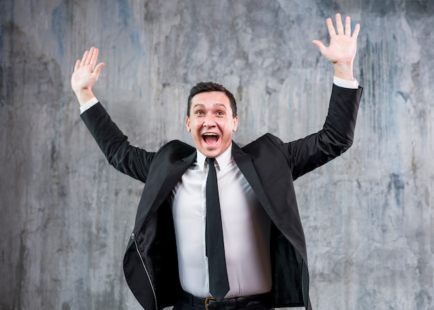 Young stylish businessman raising hands and smiling
