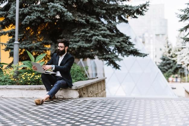 Молодой стильный бизнесмен, сидя в кампусе, используя ноутбук