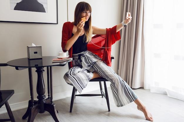 Giovane donna alla moda casual seduta nel suo salotto
