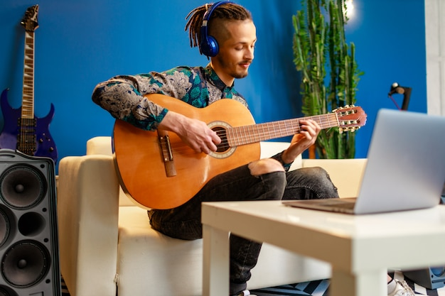 Молодой стильный кавказский человек принимая урок гитары онлайн дома используя его компьтер-книжку
