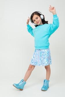 Молодая стильная очаровательная девушка в бирюзовой блузке и сапогах наслаждается музыкой в наушниках и танцует на белой стене