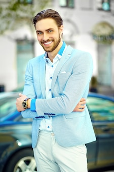 Young stylish confident happy handsome smiling businessman model man in blue suit cloth lifestyle in the street