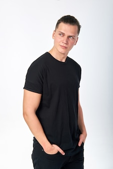 Young stylish confident smiling man wearing a black cotton short-sleeved t-shirt posing