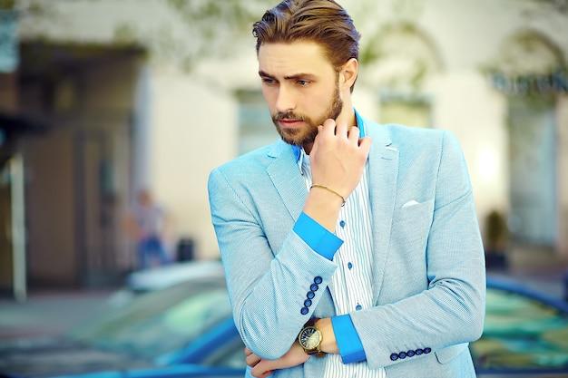 通りで青いスーツ布ライフスタイルで若いスタイリッシュな自信を持って思考ハンサムな実業家モデル男