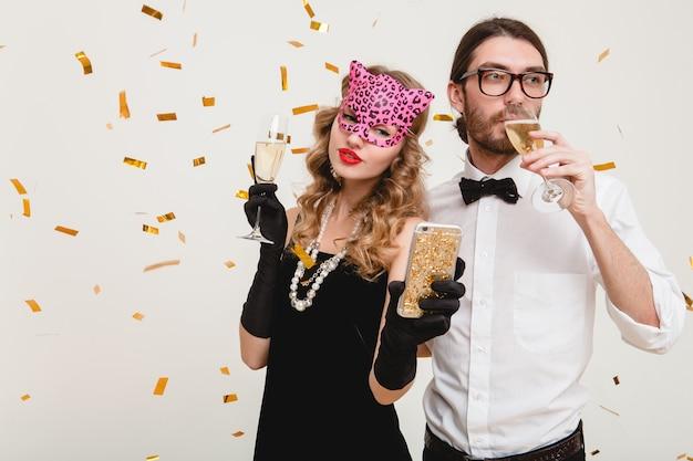 Молодая стильная влюбленная пара пьет шампанское на вечеринке