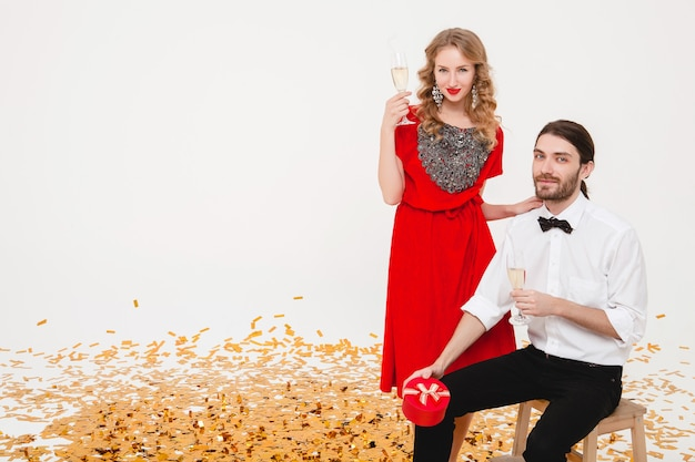 Молодая стильная влюбленная пара держит бокалы и пьет шампанское, празднуя новый год