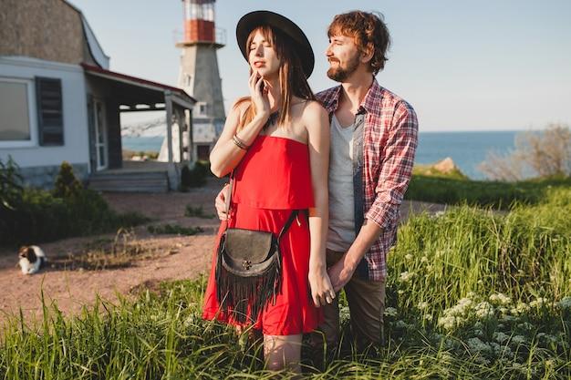 田舎、インディーヒップスターの自由奔放なスタイル、週末の休暇、夏の服装、赤いドレス、緑の草、手を繋いでいる笑顔で恋にスタイリッシュなカップル