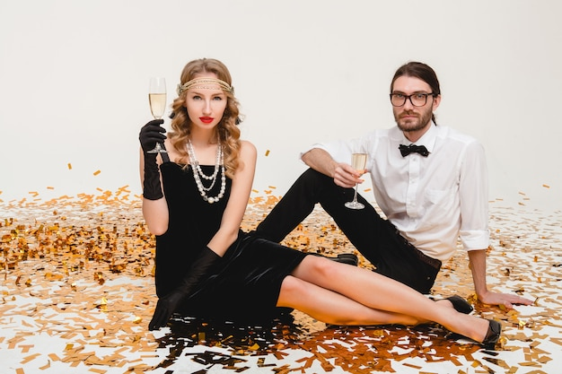 Молодая стильная влюбленная пара, сидя на полу, бросая золотое конфетти