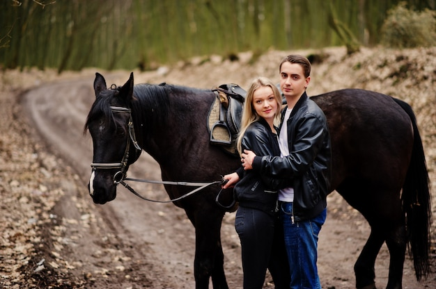 Young stylish couple in love near horse at autumn forest