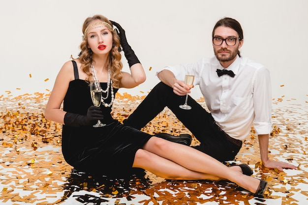 Young stylish couple in love, sitting on floor surrounded golden confetti