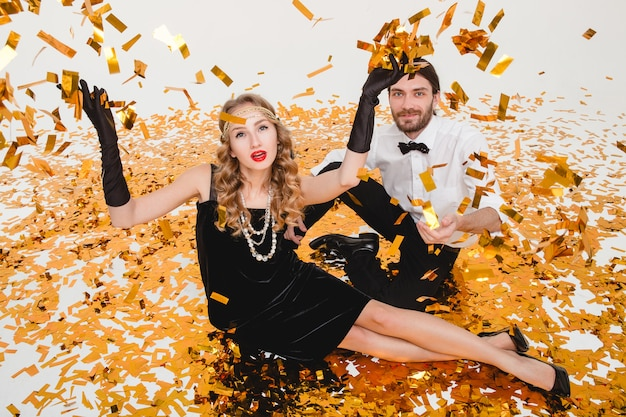 Young stylish couple in love, sitting on floor, throwing golden confetti
