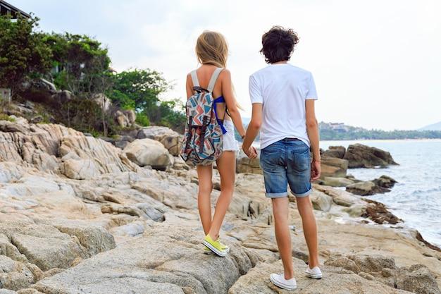 スタイリッシュな流行に敏感な夏の服とスニーカーを着て、ビーチでポーズをとってスタイリッシュなカップル。