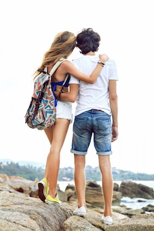 Young stylish couple posing at the beach, travel with backpack, wearing stylish hipster summer clothes and sneakers.