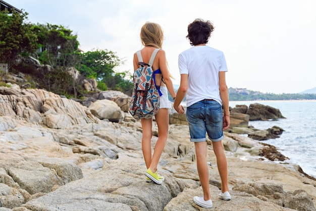 Young stylish couple posing at the beach, wearing stylish hipster summer clothes and sneakers.