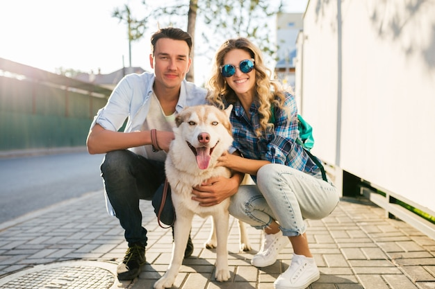 Young stylish couple posing with dog in street