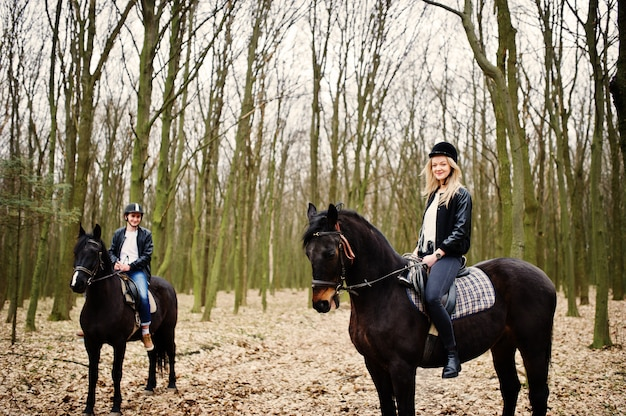 Young stylish couple riding on horses at autumn forest