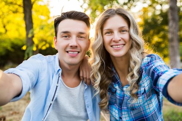 Молодая стильная пара, сидя в парке, мужчина и женщина счастливая семья вместе