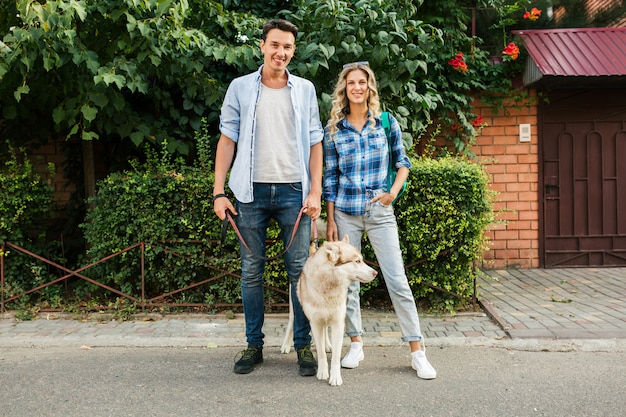 Молодая стильная пара прогулки с собакой на улице. мужчина и женщина счастливы вместе с хаски