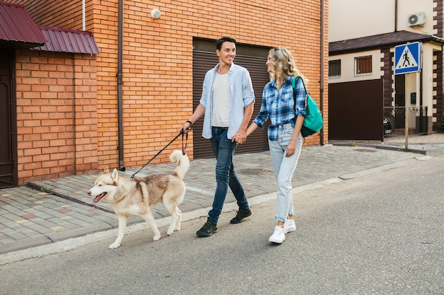 Young stylish couple walking with dog in street. man and woman happy together with husky breed,