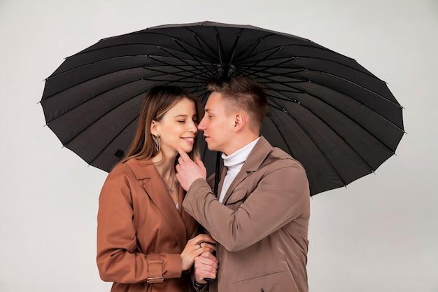 Молодая стильная пара с черным зонтиком показывает любовные эмоции. портрет милых эмоционально людей в осенней одежде, стоящих под зонтиком, глядя на светло-сером фоне. скопируйте место для сайта