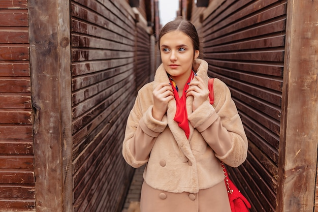 Young stylish cute girl in a fur coat strolling around the city near wooden houses and stone walls
